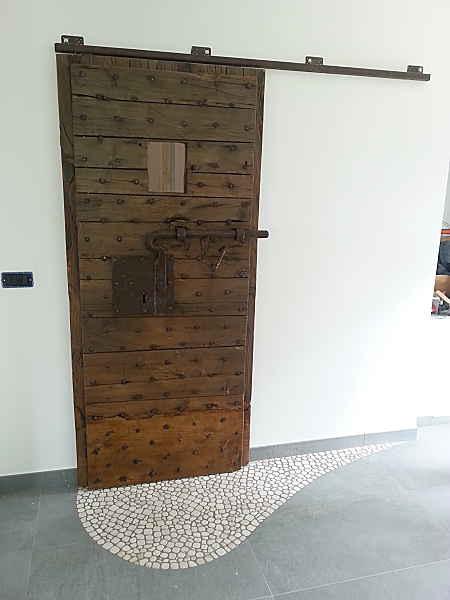 Porta scorrevole rustica con ferramenta esterna; come ambientare una porta antica scorrevole?