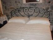 Antico sopraluce di portone diventa testiera di letto