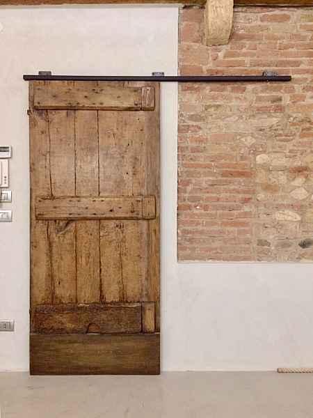Vista frontale porta antica rustica montata come scorrevole