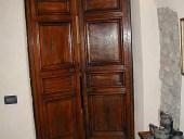 Portone antico in noce nazionale restaurato e collocato come porta di una cucina.
