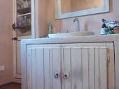 Altra vista del bagno con le antine e contorno in shabby naturale.
